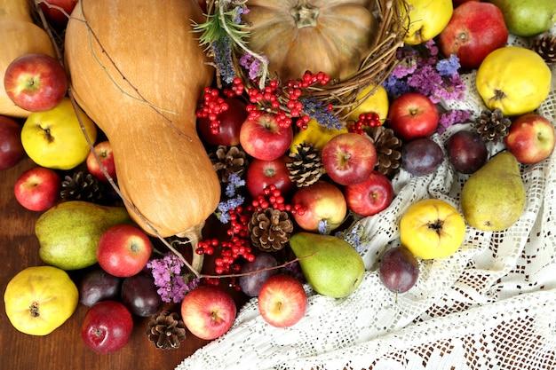 Jesienna kompozycja owoców, dyni i kwiatów na stole z bliska