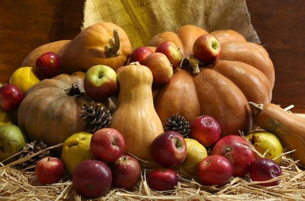 Jesienna kompozycja owoców i dyni na słomie na drewnianej ścianie