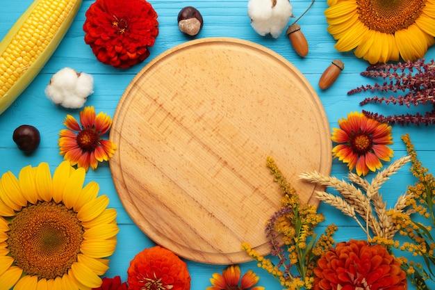 Jesienna kompozycja. rama wykonana ze świeżych kwiatów na niebieskim tle drewnianych. płaski świeckich, widok z góry, kopia przestrzeń. święto dziękczynienia
