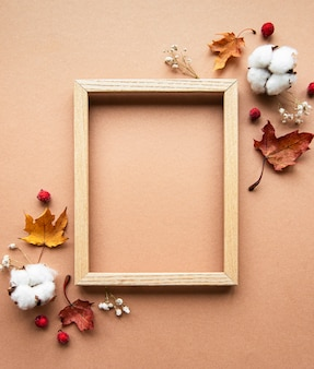 Jesienna kompozycja. ramka na zdjęcia, kwiaty, liście na brązowym tle. jesień, jesień, koncepcja święto dziękczynienia. leżał płasko, widok z góry, miejsce na kopię