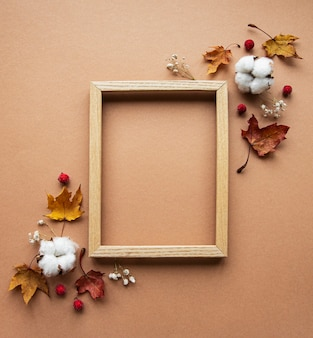 Jesienna kompozycja. ramka na zdjęcia, kwiaty, liście na brązowym tle. jesień, jesień, koncepcja święto dziękczynienia.