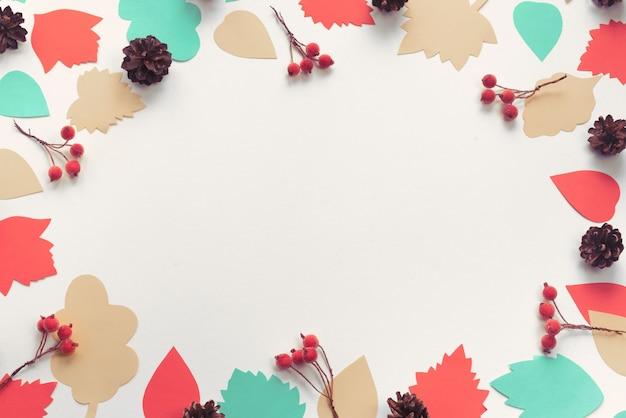 Jesienna kompozycja ramki papierowe liście kolorowe szyszki gałęzie jagody