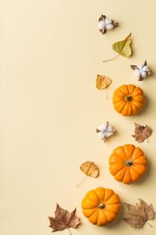 Jesienna kompozycja święto dziękczynienia z ozdobnymi pomarańczowymi dyniami i suszonymi liśćmi. płaski świecki, widok z góry, kopia przestrzeń, martwa natura na żółtym tle na kartkę z życzeniami