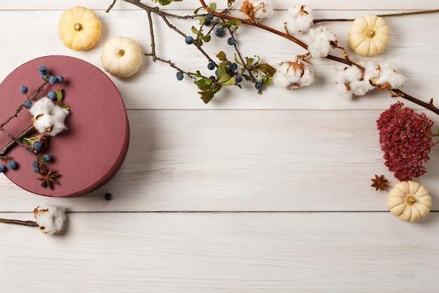 Jesienna kompozycja tła. obramowanie z suszonych jesiennych kwiatów, dyni, bawełny, anyżu, tarniny oraz zamknięte okrągłe pudełko na prezent. widok z góry na białe drewno, płaski układ