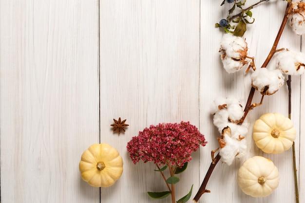 Jesienna kompozycja tła z suszonymi jesiennymi kwiatami, dyniami, gałęziami i jesiennymi liśćmi, a także bawełną, goździkami i tarniną. widok z góry