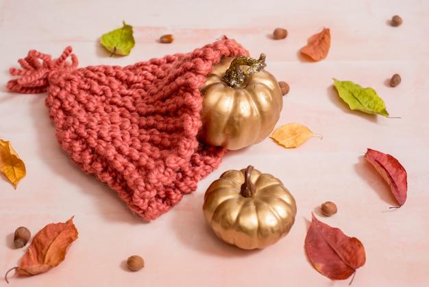 Jesienna kompozycja w stylu hygge z jasnymi ciepłymi ubraniami, filcowym kapeluszem, suchymi żółtymi liśćmi i pasiastymi dekoracyjnymi dyniami na drewnianym tle rustykalnym. łagom t. skład halloween.