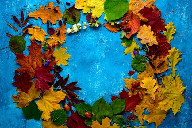Jesienna kompozycja. wieniec opadłych zielonych, żółtych, pomarańczowych i czerwonych liści w kole na turkusowym tle. jesień, opadanie liści. pozycja płaska, widok z góry, miejsce na kopię