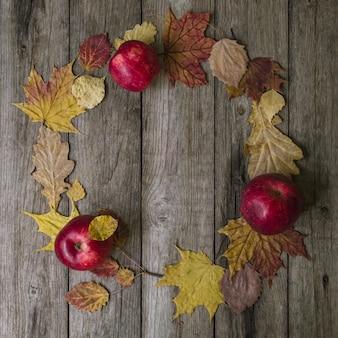 Jesienna kompozycja. wieniec z jesiennych liści i czerwonych jabłek na stare drewniane tła