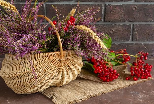 Jesienna kompozycja wrzosowej kaliny i pszenicznych kłosów w wiklinowym koszu martwa natura