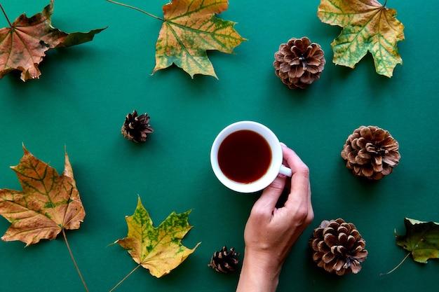 Jesienna kompozycja. wzór wykonany z październikowych suszonych liści, szyszek i tła filiżanki herbaty. szablon jesień, jesień, halloween, koncepcja święto dziękczynienia zbiorów. płaski układ, widok z góry, kopia tła miejsca