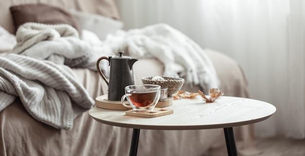 Jesienna kompozycja z filiżanką herbaty, czajnikiem i jesiennymi detalami wystroju domu na rozmytym tle.