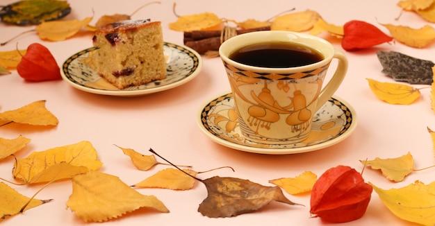 Jesienna kompozycja z filiżanką kawy, kawałkiem ciasta i ramką z cynamonu z jesiennych liści, orientacja pozioma, miejsce na kopię