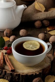 Jesienna kompozycja z gorącą herbatą na drewnianym stojaku, cynamon, psia róża, orzechy na brązowym drewnianym stole