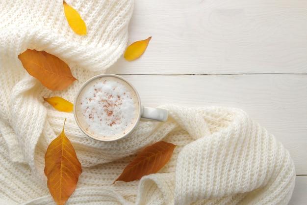 Jesienna kompozycja z gorącą kawą, ciepłym szalikiem i żółtymi listkami na białym drewnianym stole. widok z góry z miejscem na napis