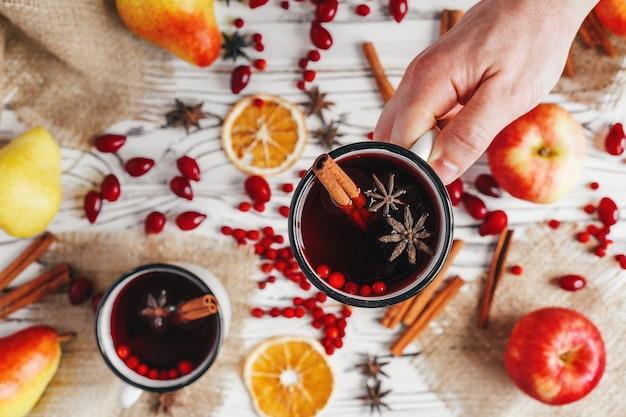 Jesienna kompozycja z gorącym grzanym winem i przyprawami na drewnianym tle