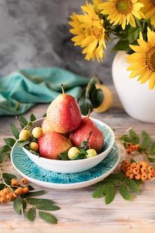 Jesienna kompozycja z gruszkami i kwiatami słonecznika na stole z drewna