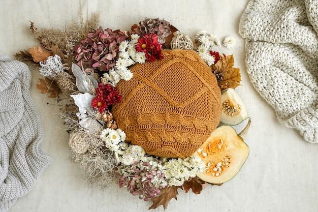 Jesienna kompozycja z kwiatami, dyniami i dzianinami kopiuje przestrzeń.