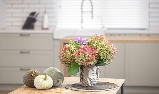 Jesienna kompozycja z kwiatów hortensji i dyni na tle wnętrza nowoczesnej kuchni.