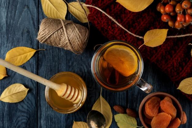 Jesienna kompozycja z miodem, orzechami i jesiennymi żółtymi liśćmi na niebieskim drewnianym stole