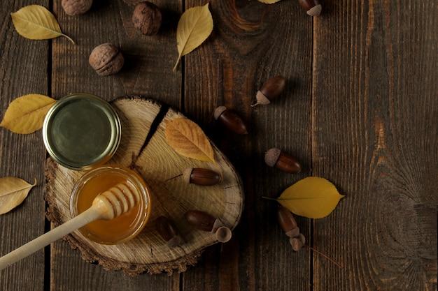 Jesienna kompozycja z miodowymi żołędziami i żółtymi liśćmi na drewnianym stojaku na brązowym drewnianym stole. widok z góry