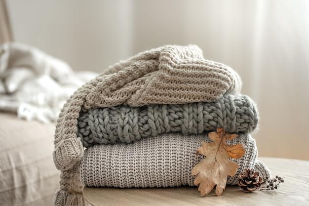 Jesienna kompozycja z przytulnymi sweterkami z dzianiny w pastelowych odcieniach i suchym liściem.