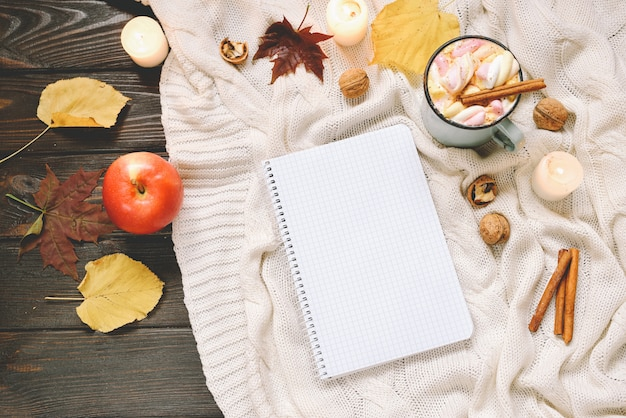 Jesienna kompozycja z suszonych liści jesienią, kakao z piankami, orzechami, cynamonem, kratą, jabłkami i otwartym zeszytem