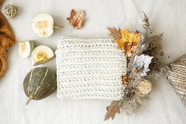 Jesienna kompozycja z suszonymi kwiatami, dynią i dzianiną w środku na białym tle.