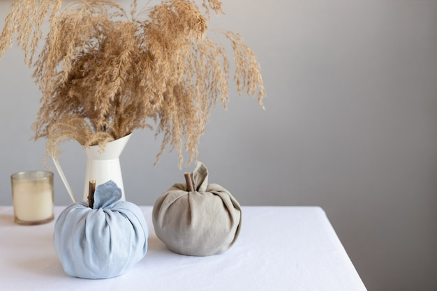 Jesienna kompozycja z tkaninowymi dyniami i trawą pampasową w dzbanku koncepcja święta dziękczynienia i halloween