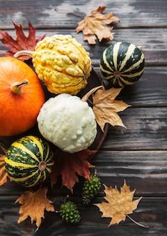 Jesienna kompozycja z wielokolorowymi dyniami na rustykalnym tle