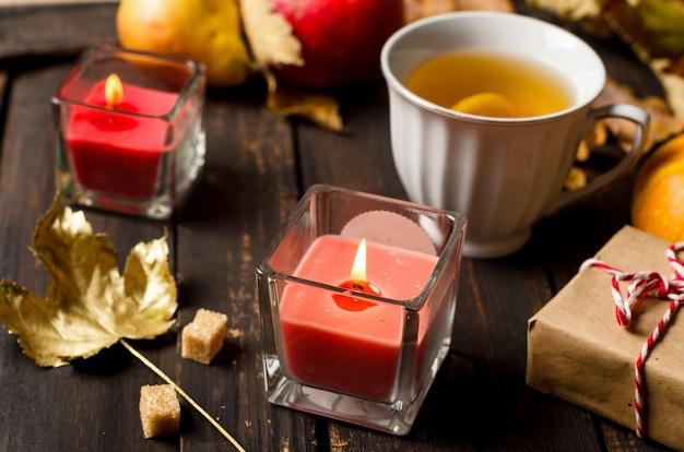 Jesienna kompozycja ze świecami, dyniami i jesiennymi liśćmi, filiżankę herbaty na ciemnym drewnianym stole w stylu rustykalnym. święto dziękczynienia i halloween. koncepcja sezonu jesiennego. jesień martwa. układanie płaskie, kopiowanie przestrzeni