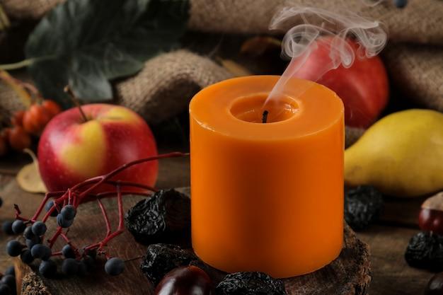 Jesienna kompozycja ze świecami i jesiennymi owocami, jagodami i kasztanami na brązowym drewnianym stole