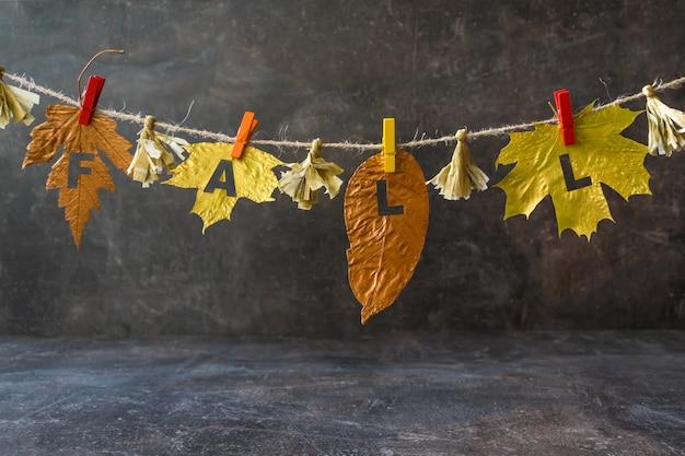 Jesienna kompozycja ze złotymi liśćmi i słowem fall