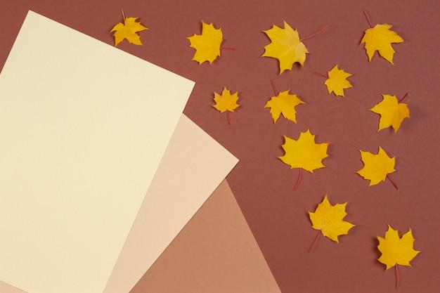 Jesienna kompozycja żółtych liści klonu na brązowym tle z miejscem na tekst