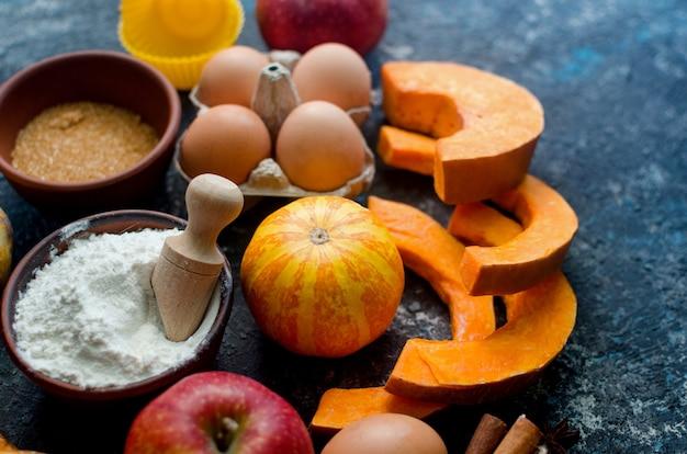 Jesienna koncepcja pieczenia. ramka z dynią, jabłkiem, orzechami, cynamonem, jajkiem i mąką na drewnianym stole. gotowanie procesu pieczenia z dodatkami. widok z góry. kopiuj przestrzeń,