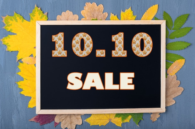 Jesienna koncepcja sprzedaży. koncepcja czarny piątek. data 10 października. jesienny kalendarz wyprzedaży. czarna ramka z napisem 10.10 sprzedaż na tle z jesiennymi liśćmi na drewnianym niebieskim tle.