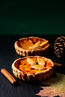 Jesienna koncepcja żywności domowej roboty organiczne rustykalne ciasto z dyni udekoruj jesienią na czarnym tle z miejsca na kopię