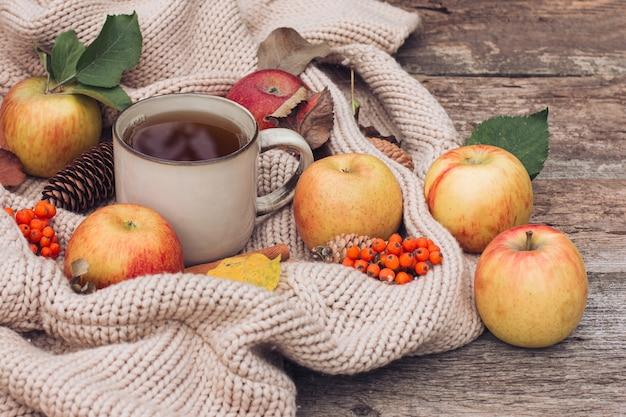 Jesienna martwa natura, filiżanka herbaty, świeży plon czerwonych i zielonych jabłek, szyszki, laski cynamonu, czerwona jarzębina, na teksturowanej dzianinie i starym drewnianym stole. jesień, jesienny nastrój i wygoda