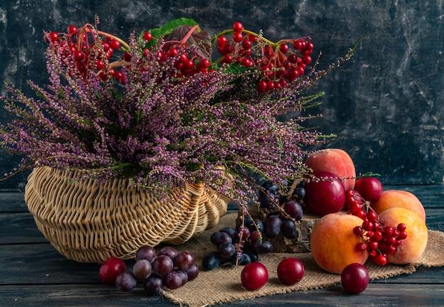 Jesienna martwa natura na czarnym tle kosz z wrzosem, kaliną i owocami