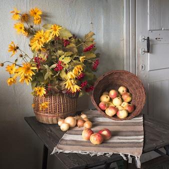 Jesienna martwa natura w rustykalnym stylu retro. kalina i żółte kwiaty w wiklinowym koszu z jabłkami i cebulą na drewnianym tle.