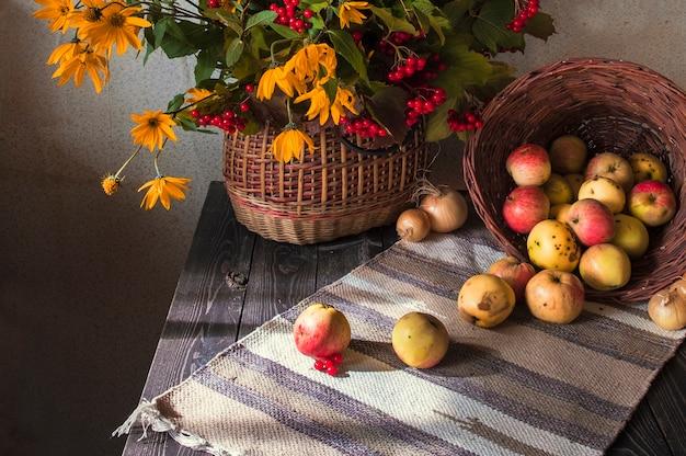 Jesienna martwa natura w rustykalnym stylu retro. kalina i żółte kwiaty w wiklinowym koszu