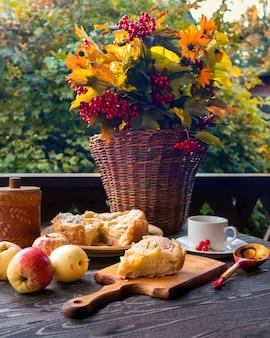 Jesienna martwa natura w rustykalnym stylu retro z szarlotką i herbatą kalina i żółte kwiaty w wiklinowym koszu