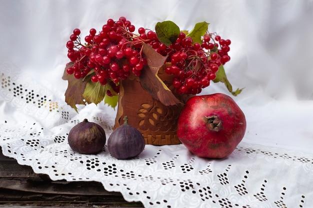 Jesienna martwa natura w stylu rustykalnym z czerwoną żurawiną, granatem i figami