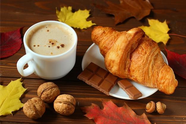 Jesienna martwa natura z cappuccino i rogalikiem