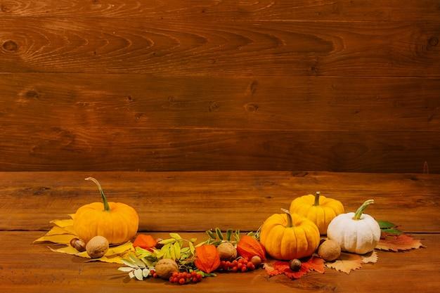 Jesienna martwa natura z dyniami i żółtymi liśćmi świąteczna dekoracja na święto dziękczynienia