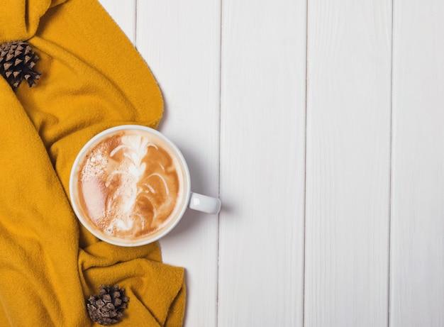Jesienna martwa natura z gorącym cappuccino i żółtym swetrem.