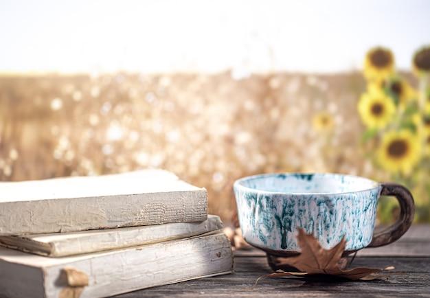 Jesienna martwa natura z książkami i pięknym kubkiem na niewyraźnym tle pola i słoneczników.