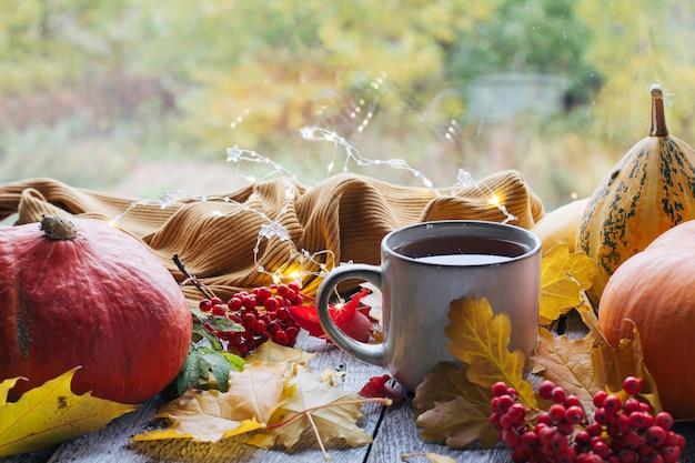 Jesienna martwa natura z pięknym bokeh jesiennymi liśćmi i filiżanką gorącej kawy lub herbaty pomarańczowej dyni...