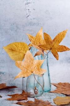 Jesienna martwa natura ze szklanymi butelkami i liśćmi
