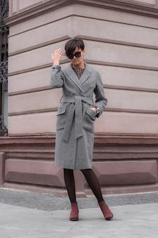 Jesienna moda. brunetka z krótkimi włosami w modnym stylowym szarym płaszczu i okularach przeciwsłonecznych, pozuje na tle budynku. moda uliczna.