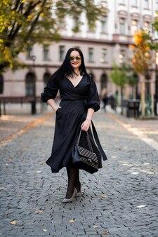 Jesienna moda. dziewczyna z czerwonymi ustami w modnej stylowej czarnej sukience i okularach przeciwsłonecznych, styl życia na tle rozmytych żółtych zielonych drzew w parku.